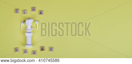 White Headphones With Small Statue And Text Clubhouse On Yellow Background. Top View Flat Lay Copy S