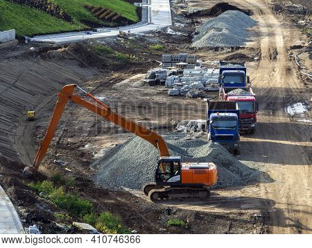 Landscaping, Road Asphalting. The Excavator Digs The Ground. Dump Trucks Brought Gravel. There Are S
