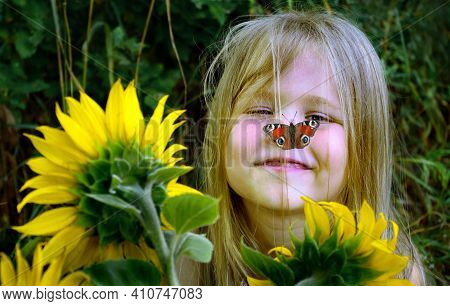 Summer Concept. Colorful Red Butterfly And A Girl With Flowers. Child Among Flowers. Girl With Sunfl