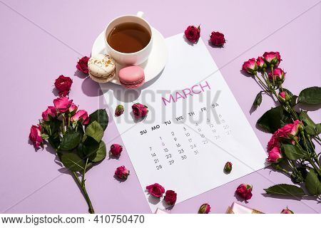 Cup Of Tea Is On The Calendar With A Mark For March 8. Rose Petals Are Scattering On The Surface On