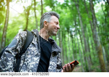 Mature man walking and hiking in mountain forest and using mobile phone. Male spring outdoor portrait.