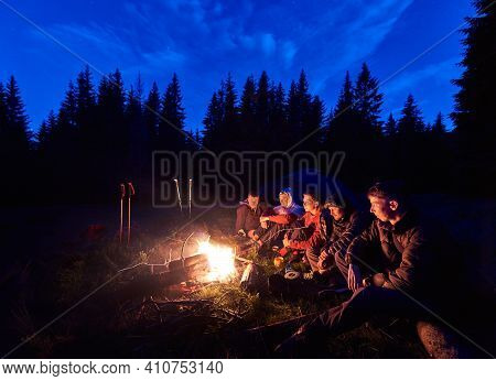 Company Of Young People Is Sitting Around The Fire Against The Backdrop Of The Silhouetted Of Large