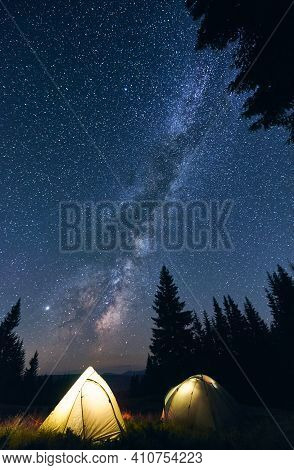 Vertical Shot Of Tourist Camping In Forest, Warm Summer Evening. Two Illuminated Tents Under Beautif