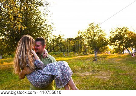 Happy Young Couple. Girl At The Hands Of Man. A Loving Couple Walking In The Autumn Or Summer. Coupl
