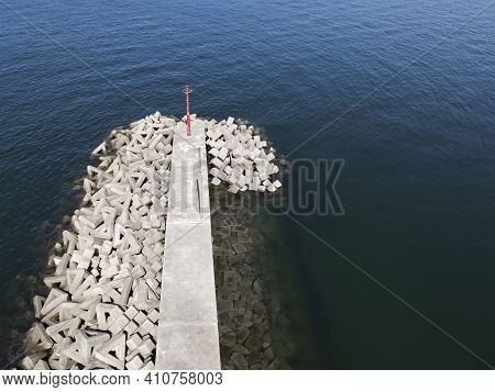 Aerial View Of Jetty With Concrete Blocks, White Jetty Against Blue Water