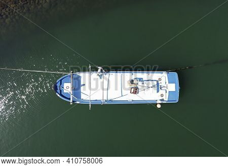 Aerial View Of Fishing Boat Moored Against A Background Of Deep Green Sea Water