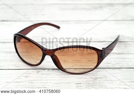 Ladies Fashion Sunglass On A White Wooden Table
