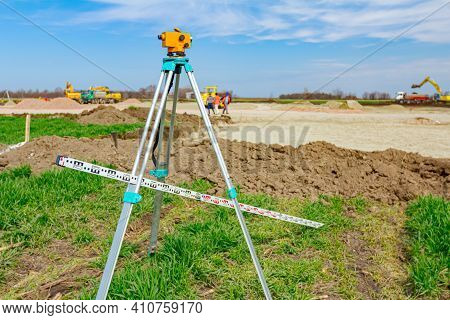 Surveyor Instrument And Leveling Lath Are Used For Measuring Level On Construction Site. Surveyors E