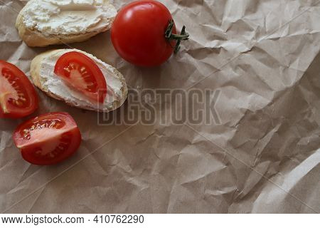 Spreadable Bread With Curd Cheese On A Mint Paper Background With Slices Of Ripe Juicy Tomato. A Who