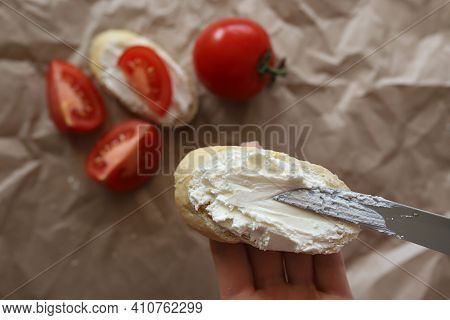 Curd Cheese Is Spread With A Knife On A White Slice Of Bread.