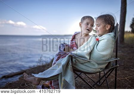Family Local Getaway. Kids Covering With Towels Sitting On The Camping Armchair At Campsite And Look
