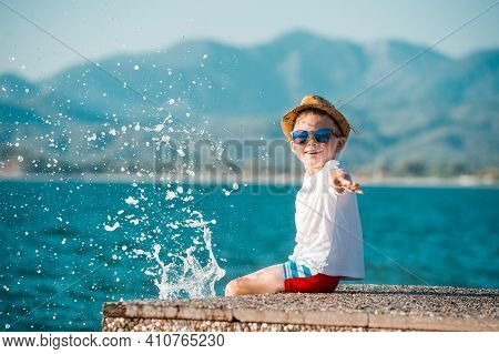 Little Happy Boy In Blue Sunglasses And Hat Has A Big Smile On His Face. Beautiful Landscape And Bri
