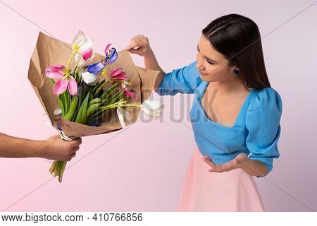 A Mans Hand Gives A Bouquet Of Wilted Tulips To A Girl On A Pink Background. The Young Girl Is At A