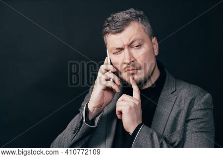 Man Standing With Hand On Chin Thinking About Question During Phone Call, Pensive Expression. Though