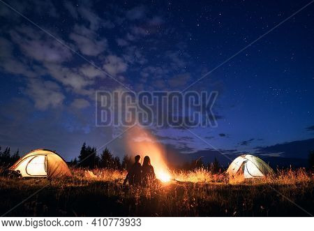 Fantastic View Of Night Starry Sky Over Grassy Hill With Illuminated Camp Tents, Campfire And Hikers