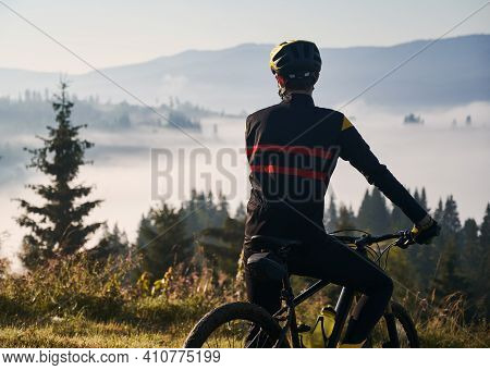 Back View Of Man In Cycling Suit Standing With Bicycle On The Hill. Male Bicyclist In Safety Helmet