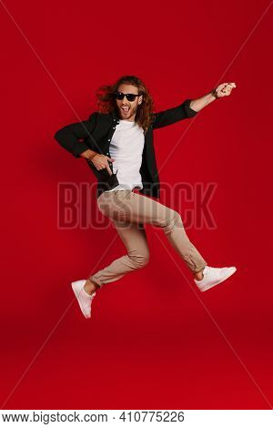 Full Length Of Playful Young Man In Casual Clothing Smiling And Playing Imaginary Guitar While Hover