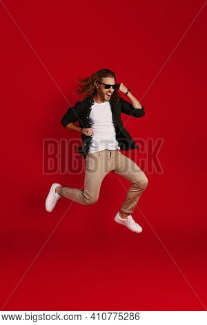 Full Length Of Happy Young Man In Casual Clothing Smiling And Gesturing While Hovering Against Red B