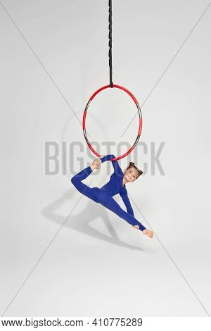 Little Child Girl Gymnast In Sportwear Doing Twine On An Aerial Hoop