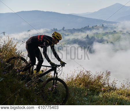 Young Sportsman Riding His Bike In The Mountains In Early Foggy Morning Going Downhill. Concept Of A