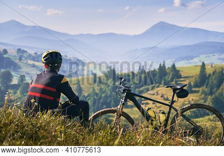 Young Man In Safety Helmet Sitting On Grass Near Bicycle And Looking At Beautiful Misty Mountains. M