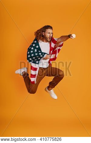 Confident Young Man In Casual Clothing Making A Face And Punching While Hovering Covered In American