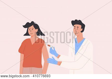 Male Doctor In A Medical Gown And Gloves Gives Vaccine Shot To Female Patient. Vaccination Campaign.