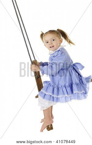 An adorable preschooler in an old fashioned dress and bloomers swinging high on an antique, wooden, self-pumping swing.  On a white background.