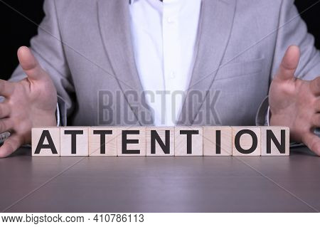 Attention, The Word Is Written On Wooden Cubes, Blocks On The Background Of A Man, A Businessman In