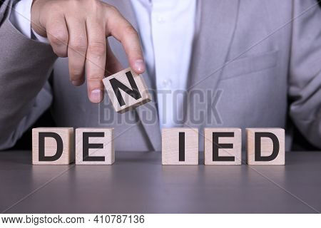 Denied, The Word Is Written On Wooden Cubes, Blocks On The Background Of A Man, A Businessman In A G