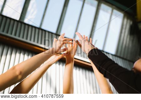Conceptual Image Of Teamwork And Cooperation With A Group Of People Raising Their Hands And Placing