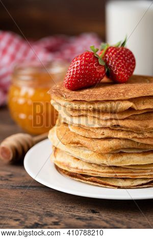 Stack Of Thin French Crepes Served With Strawberries And Honey. Rustic Style