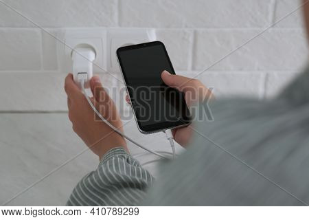 Woman With Mobile Phone Plugging Charger In Socket On White Brick Wall, Closeup