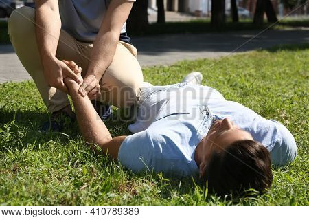 Passerby Checking Pulse Of Unconscious Man Outdoors. First Aid