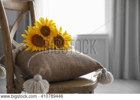 Bouquet Of Beautiful Sunflowers And Cushion On Chair Indoors