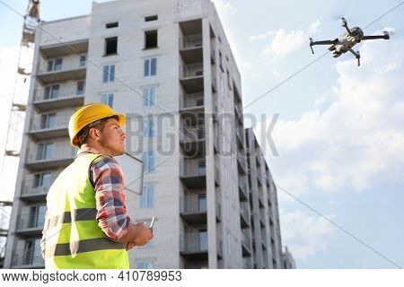 Builder Operating Drone With Remote Control At Construction Site. Aerial Photography