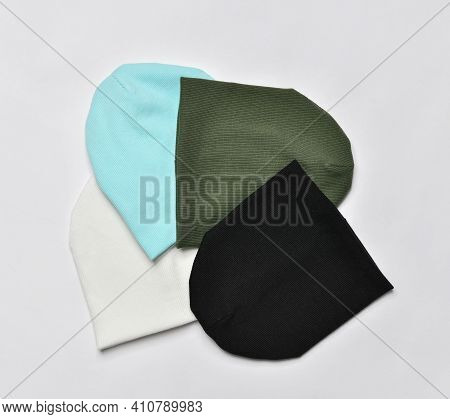 Set Of Four Modern Knitted Beanie Hats, Green, Black, White Mint, Light Blue Knitwear Isolated On Wh