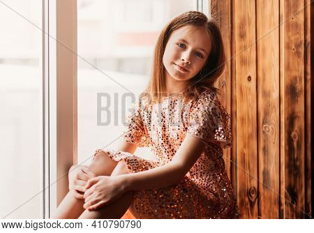 A Beautiful Teenage Girl In A Dress Sits On The Windowsill. A Look At The Camera