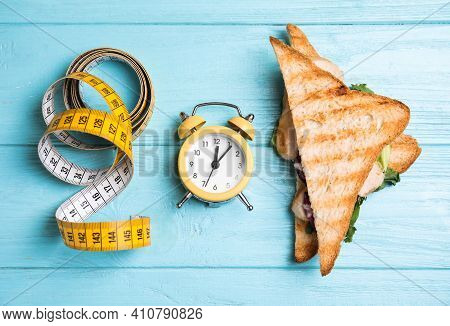 Tasty Sandwich, Alarm Clock And Measuring Tape On Light Blue Wooden Table, Flat Lay. Diet Regime