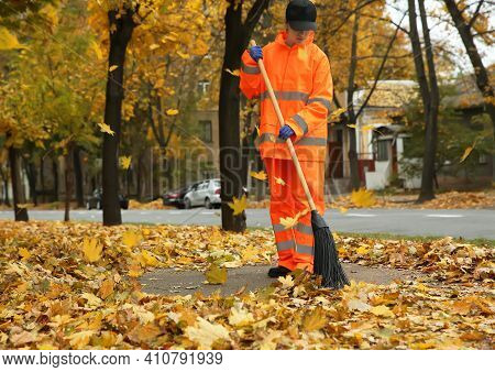 Street Cleaner Sweeping Fallen Leaves Outdoors On Autumn Day