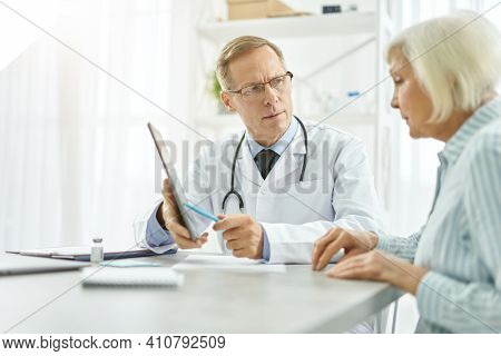Serious Male Doctor Having Appointment With Old Woman In Clinic