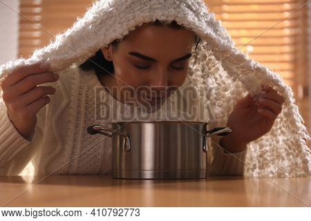 Woman With Plaid Doing Inhalation Above Saucepot At Table Indoors