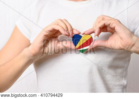 Seychelles Flag In The Shape Of A Heart In The Hands Of A Girl. Love Seychelles. The Concept Of Patr