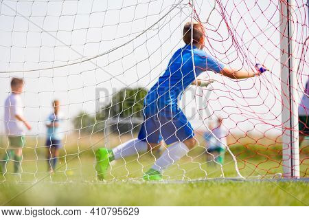 Football Goalkeeper Running And Catching Ball In A Goal. View From Backside. Soccer Net. Young Boys