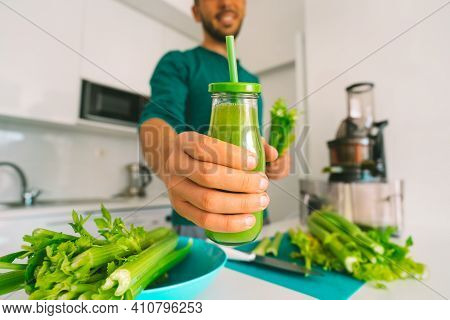 Healthy Man Making Fresh Detox Homemade Celery Juice In Juicer Machine At Home And Holding A Glass B