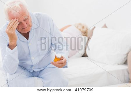 Old man looking at pills while woman sleeping on the bed