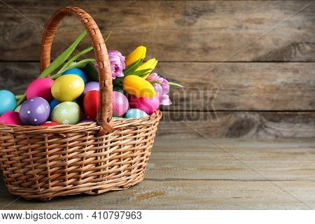 Colorful Easter Eggs And Tulips In Wicker Basket On Wooden Background. Space For Text