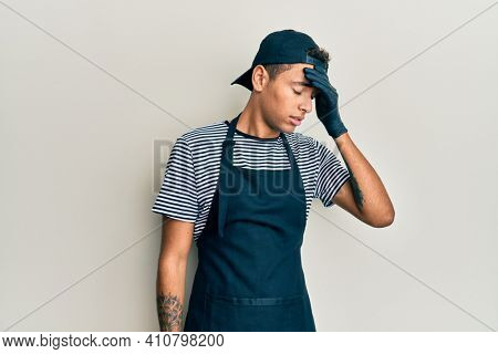 Young handsome african american man tattoo artist wearing professional uniform and gloves surprised with hand on head for mistake, remember error. forgot, bad memory concept.