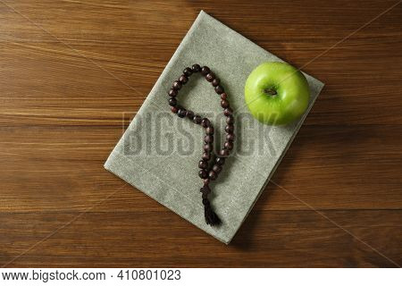 Rosary Beads And Apple On Wooden Table, Top View. Lent Season
