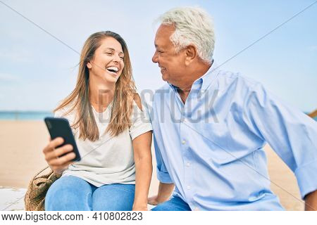 Middle age hispanic couple using smartphone sitting on the bench at the beach.